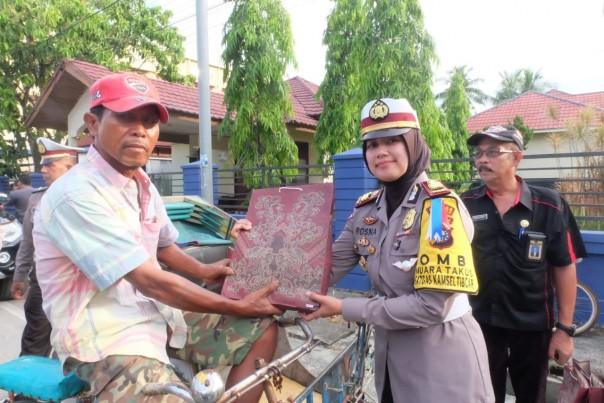 Bersama Sekretaris Kesbangpol Inhil, Kasat Lantas Bagi-bagi Bunga dan Sembako